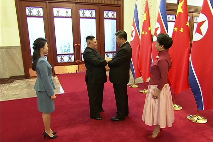 Footage released by China Central Television (CCTV) on January 10, 2019 shows China President Xi Jinping (2nd R) greeting North Korean leader Kim Jong Un (2nd L), in the Great Hall of the People in Beijing on January 8, 2019.  (Photo by CCTV / AFP)