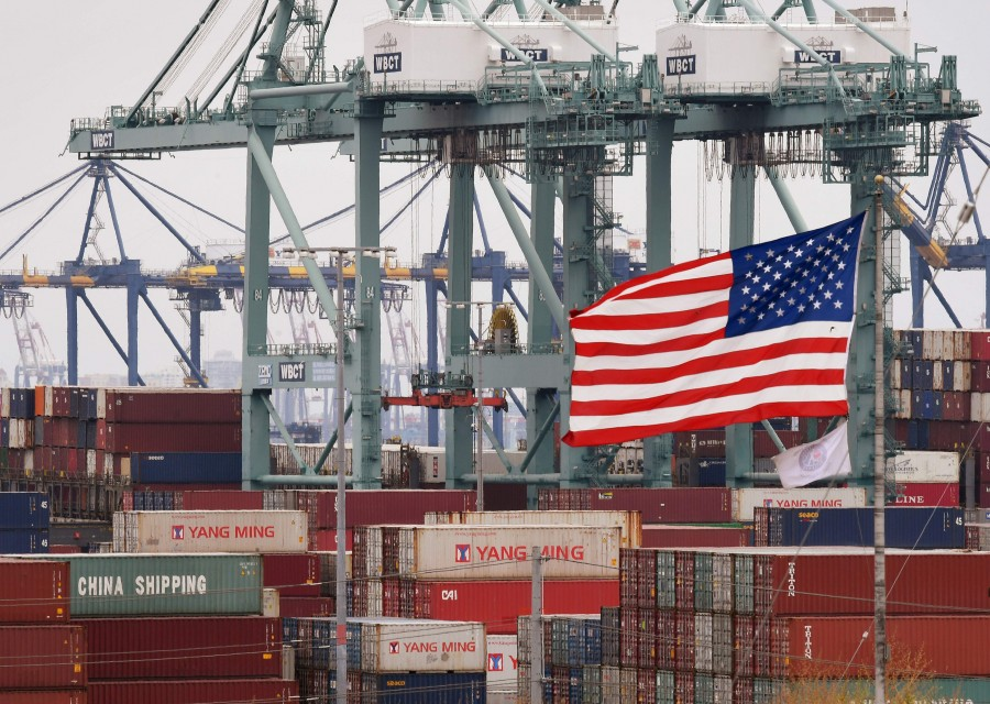 Chinese shipping containers are stored beside a US flag after they were unloaded at the Port of Los Angeles in Long Beach, California on May 14, 2019. (Photo by Mark RALSTON / AFP)