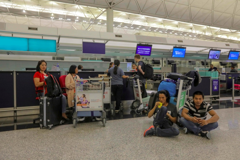 Stranded passengers sit near check-in counters as all flights have been cancelled after protesters occupied Hong Kong international airport following a protest on August 12, 2019. (Photo by VIVEK PRAKASH / AFP)